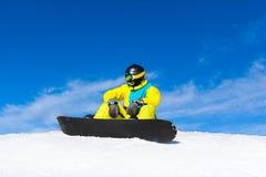 Snowboarder sitting on snow mountain slope Royalty Free Stock Photos