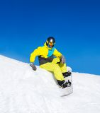 Snowboarder sitting on snow mountains Stock Photos
