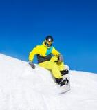 Snowboarder sitting on snow mountains Stock Photos