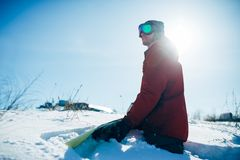 Snowboarder sitting on snowy slope in sunny day. Snowboarder in glasses sitting on snowy slope in sunny day. Winter extreme sport, active lifestyle. Snowboarding Royalty Free Stock Images