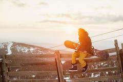 Snowboarder sitzt auf Zaun mit Snowboard Stockfotos