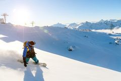 A snowboarder in a ski mask and a backpack is riding on a snow-covered slope leaving behind a snow powder against the