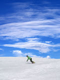 Snowboarder on ski slope and blue sky Stock Photo