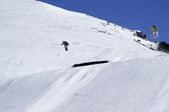 Snowboarder and skier jumping in snow park at ski resort on sunn Stock Images