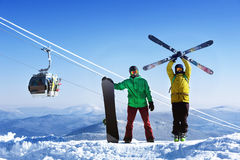 Snowboarder and skier on mountain. Against ski lift Royalty Free Stock Photography