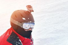 Snowboarder or skier portrait in sport goggles and protection helmet with mounted action camera and ski slope on background. Exreme winter sport outdoor stock image