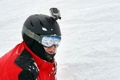 Snowboarder or skier portrait in sport goggles and protection helmet with mounted action camera and ski slope on background. Exreme winter sport outdoor stock images
