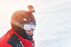 Snowboarder or skier portrait in sport goggles and protection helmet with mounted action camera and ski slope on background. Exreme winter sport outdoor stock photos