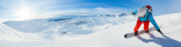 Snowboarder skiing downhill, panoramic format stock image