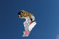 Snowboarder in the sky. Pro snowboarder jumping from giant trampoline of Buttermilk resort in Aspen, Colorado Stock Photos