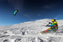 Snowboarder skydives on blue sky backdrop in snow mountains Royalty Free Stock Photo