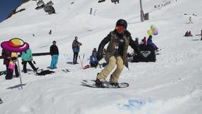 Snowboarder slide on iron trail, but fail. Ski resort. Sunny day. Extreme sport