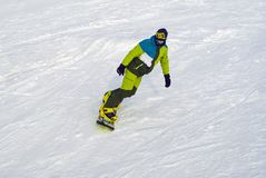 Snowboarder slides down a slope against the background of snow royalty free stock photography