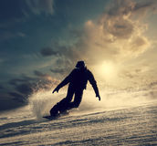 Snowboarder slides down the snowy hill Stock Images