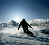 Snowboarder slides down the snowy hill Royalty Free Stock Photo