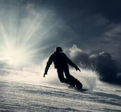 Snowboarder slides down the snowy hill Royalty Free Stock Photography