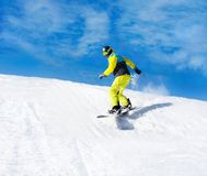 Snowboarder sliding down the hill, snow mountains Stock Photo