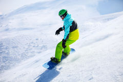 Snowboarder sliding down a slope royalty free stock photo