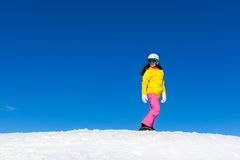 Snowboarder sliding woman down hill, snow Stock Photo