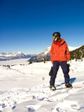 Snowboarder on the slope. Young man on the snowboard under the bright sun royalty free stock photo