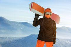 Snowboarder snowboard portrait mountain top orange. Snowboarder with snowboard orange portrait against mountains. Sheregesh ski resort Stock Images