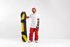 Snowboarder with snowboard in studio. Cool rider in plain white t-shirt, red snowboard pants and red beanie holding a snowboard on white stock image