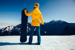 Snowboarder with snowboard on winter mountain top. One snowboarder ready for snowboarding on winter mountain top Stock Images