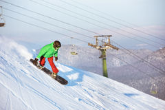 Snowboarder snowboarding riding downhill sheregesh. Snowboarder riding downhill against ski lift. Sheregesh snowboarding and skiing resort Stock Images