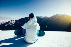 Snowboarder snowboarding in winter mountains. One young woman snowboarder ready for snowboarding on winter mountain top Stock Images