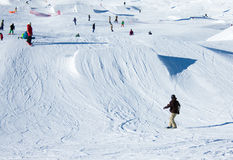 Snowboarder at snowpark. Snowboarder going down the slope at a snowpark in Madonna di Campiglio in Italian Alps Stock Photos
