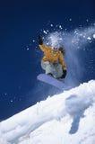 Snowboarder sobre cuesta con el polvo de la nieve que se arrastra detrás Foto de archivo