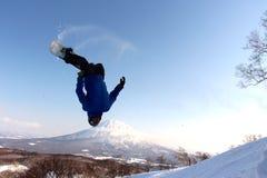 Snowboarder som överför det av backcountry hopp Royaltyfri Foto