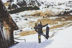 Snowboarder som bär det svarta omslaget, maskering med det autentiska trähuset för snowboardslut Man som ser panorama- mountans arkivfoto