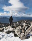 Snowboarder som bara står på toppmötet som stirrar ner på Lake Tahoe och för snö korkade berg royaltyfria foton