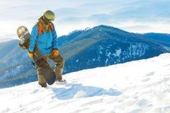 Snowboarder som går till det mycket bästa av ett berg på den guld- timmen Arkivbild