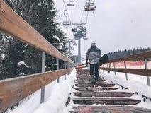 Snowboarder som går upp trappan i skidarapporten Vit bakgrund Fotografering för Bildbyråer