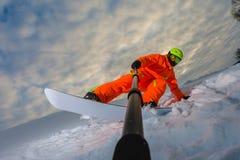 Snowboarder som gör ett trick och gör en selfie royaltyfri foto