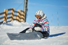Snowboarder som sitter i snlowen royaltyfri fotografi