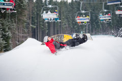 Snowboarder spada na skłonach podczas doskakiwania Obraz Royalty Free