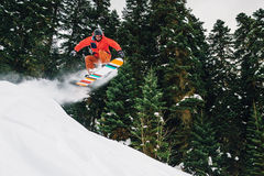 Snowboarder with special equipment is jumping hight and freeriding. Snowboarder with special equipment is jumping very high and freeriding in the mountain forest Royalty Free Stock Images
