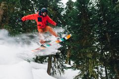 Snowboarder with special equipment is riding and jumping very fast in the mountain forest Stock Image