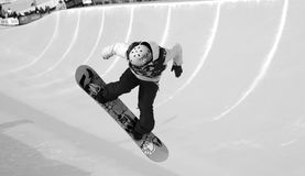 Snowboarder Spinning into the pipe in B/W half-pipe competition, Mammoth Mountain, California USA. Professional snowboarder set against the indicator lines of Royalty Free Stock Image