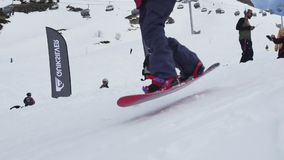 Snowboarder springen vom Sprungbrett und fahren auf Steigung Leute Makro des grünen Grases sonnig stock video footage