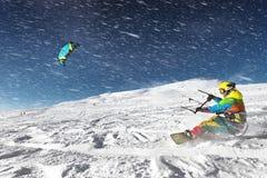 Snowboarder springt auf Hintergrund des blauen Himmels in den Gebirgsschneefällen im freien Fall stockfoto