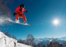 Snowboarder springt met snowboard van snowhill Stock Fotografie