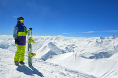 Snowboarder standing with board high in the mountains i Royalty Free Stock Photos