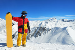 Snowboarder standing with board high in the mountains i Royalty Free Stock Images