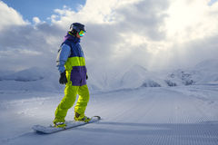Snowboarder standing on the board in the mountains Stock Photography