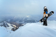 Snowboarder standing on  cliff in  snowy weather in the mountains. Stock Photos