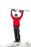 Snowboarder standing with snowboard raised overhead Royalty Free Stock Image